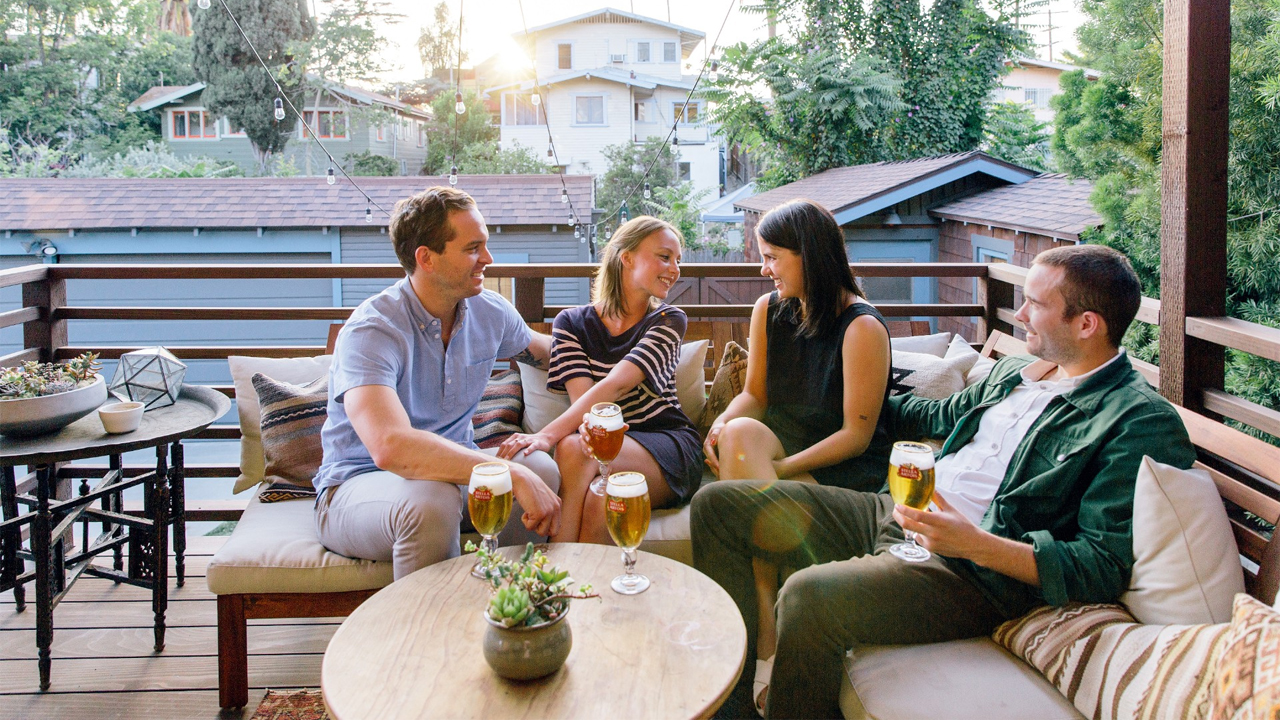 Four people sit around a table drinking beer. Stella Artois practices corporate social responsibility by expanding access to clean drinking water around the world.
